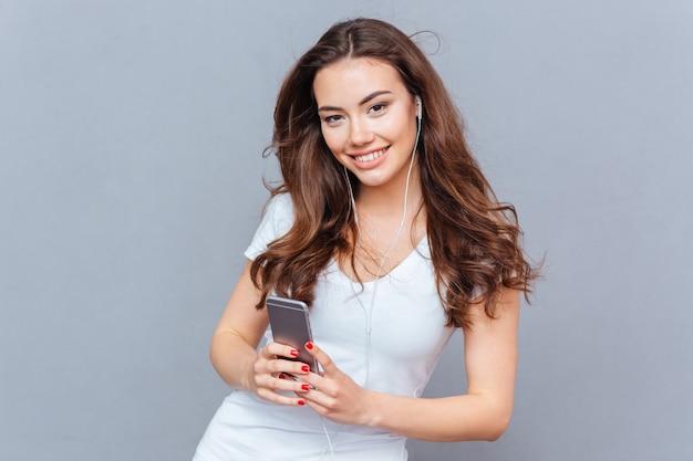 Uśmiechnięta ładna młoda kobieta słuchająca muzyki ze smartfona na szarym tle