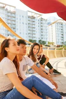 Uśmiechnięta ładna młoda kobieta spędzająca czas z najlepszymi przyjaciółmi siedząca na moście i ciesząca się dobrą pogodą