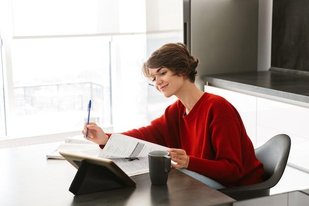 Uśmiechnięta ładna młoda kobieta studiuje z komputerem typu tablet przy stole w kuchni w domu