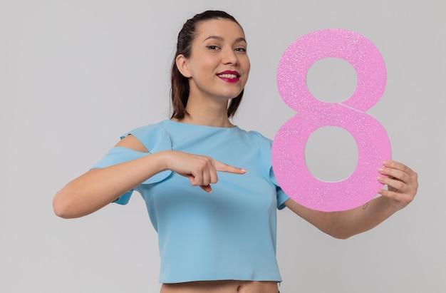 Uśmiechnięta ładna młoda kobieta trzymająca i wskazująca na różową cyfrę osiem
