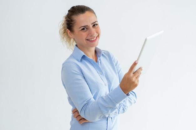 Uśmiechnięta ładna młoda kobieta używa pastylka komputer