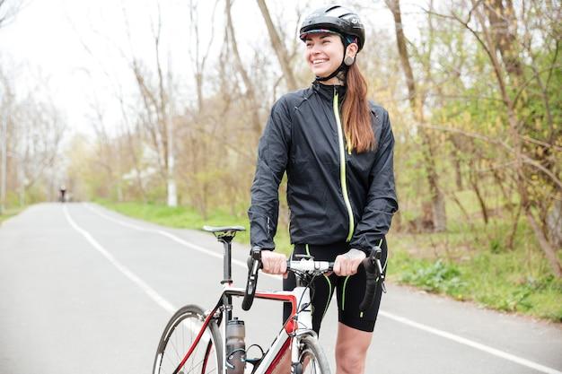 Uśmiechnięta ładna młoda kobieta z rowerem chodząca po drodze