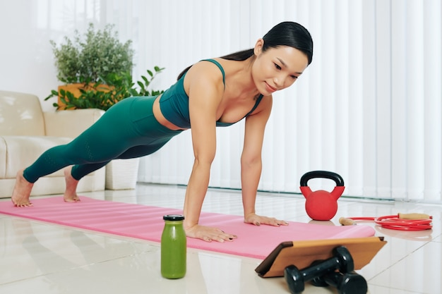 Uśmiechnięta ładna młoda wietnamka stojąca w pozycji deski i oglądająca trening wideo na tablecie