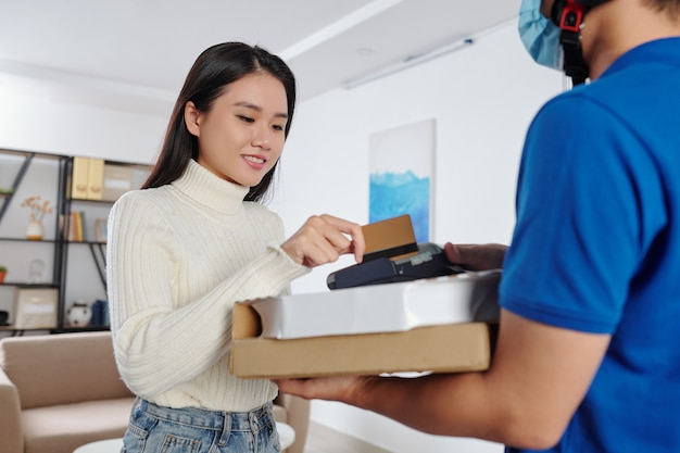 Uśmiechnięta ładna młoda wietnamka wyciągająca kartę kredytową, aby zapłacić kurierowi za dostawę pizzy