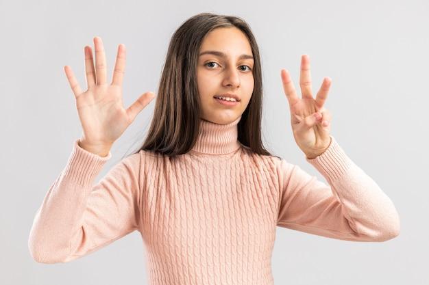 Uśmiechnięta ładna nastolatka patrząca na kamerę pokazującą numer osiem palcami na białym tle na białej ścianie z miejscem na kopię