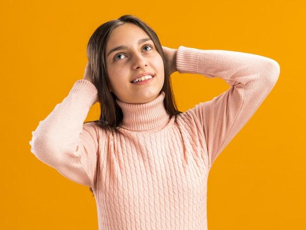Uśmiechnięta ładna nastolatka patrząca w górę trzymająca ręce za głową odizolowana na pomarańczowej ścianie