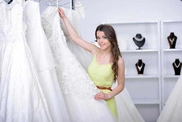 Uśmiechnięta ładna panna młoda wybiera białą suknię w sklepie.