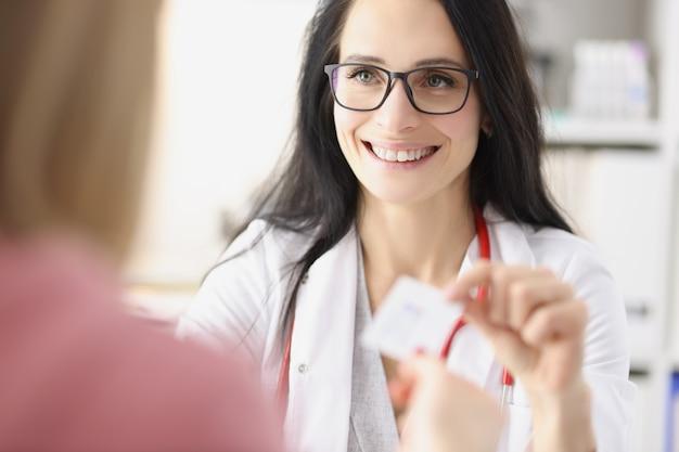 Uśmiechnięta lekarka dająca wizytówkę pacjentowi w recepcji w klinice osobisty lekarz