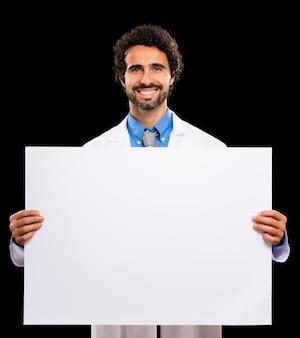 Uśmiechnięta lekarka pokazuje białego prześcieradło papier. czarne tło