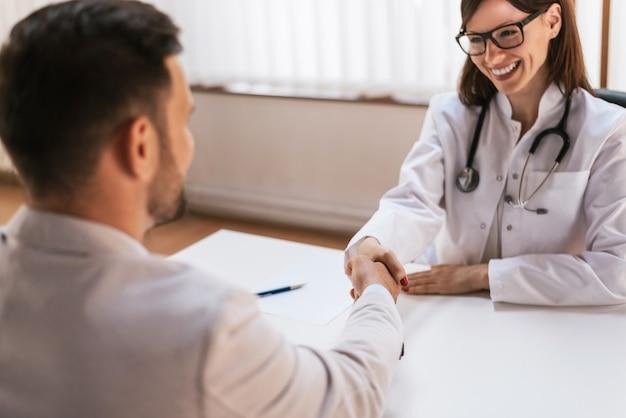 Uśmiechnięta lekarka przy kliniką daje uściskowi dłoni jego pacjent