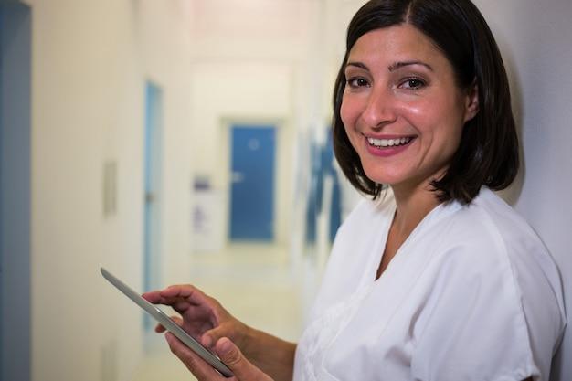 Uśmiechnięta lekarka używa cyfrową pastylkę przy kliniką