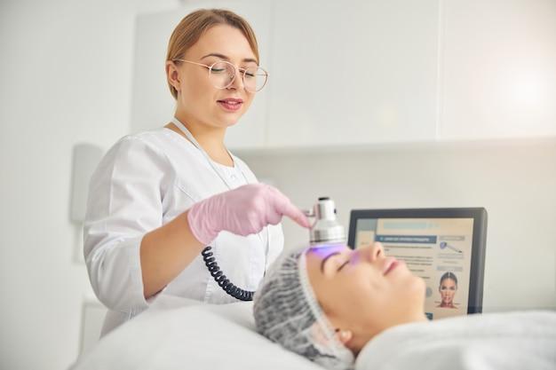 Uśmiechnięta lekarka w okularach, używająca fioletowej długości fali światła do leczenia stanu skóry pacjenta patient