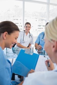 Uśmiechnięta lekarka w pokoju konferencyjnego mienia falcówce