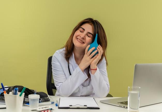 Uśmiechnięta lekarka w średnim wieku ubrana w szlafrok medyczny i stetoskop siedząca przy biurku z narzędziami medycznymi i laptopem trzymająca lewatywę w pobliżu głowy z zamkniętymi oczami na białym tle