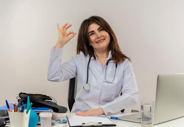 Uśmiechnięta lekarka w średnim wieku ubrana w szlafrok medyczny ze stetoskopem siedząca przy biurku praca na laptopie z narzędziami medycznymi pokazująca gest okey na izolowanym białym backgroung z miejscem na kopię