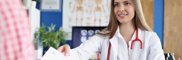 Uśmiechnięta lekarka wręcza pacjentowi receptę na medynę