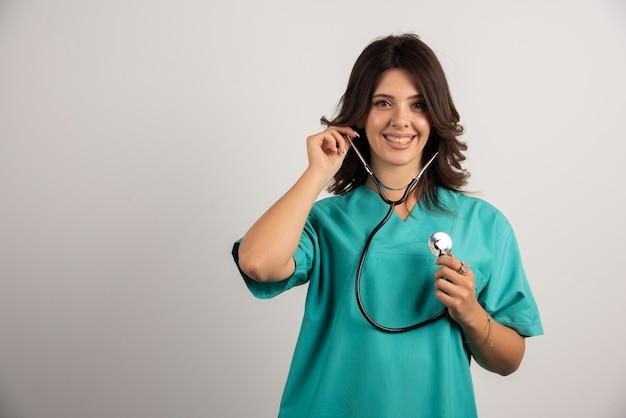 Uśmiechnięta lekarka z stetoskopem pozuje na bielu.