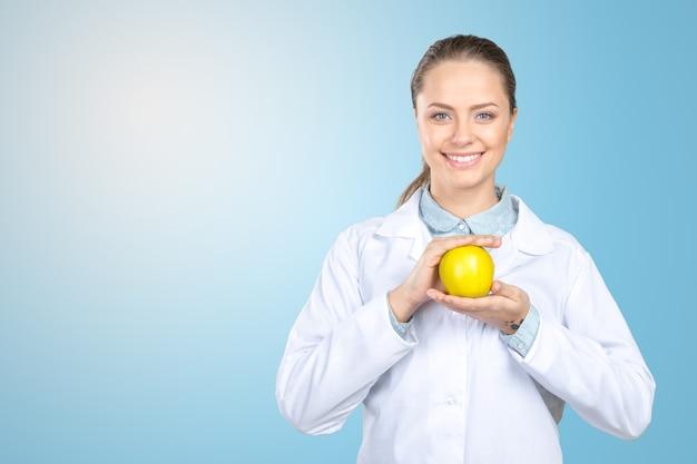 Uśmiechnięta lekarz medycyny kobieta z jabłkiem