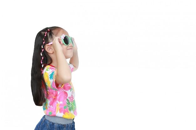 Uśmiechnięta mała azjatycka dziecko dziewczyna jest ubranym kwiecistą deseniową lato suknię i okulary przeciwsłonecznych