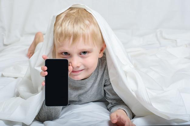 Uśmiechnięta mała blond chłopiec z smartphone. leżąc w łóżku i chowając się pod kołdrą. gadżet wypoczynek