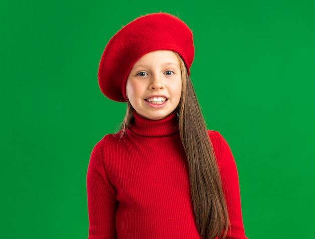 Uśmiechnięta mała blondynka ubrana w czerwony beret patrząc na przód na zielonej ścianie z kopią przestrzeni
