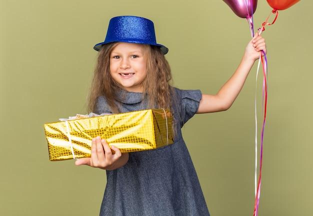 Uśmiechnięta mała blondynka w niebieskim kapeluszu imprezowym, trzymająca balony z helem i pudełko na prezent na oliwkowozielonej ścianie z miejscem na kopię