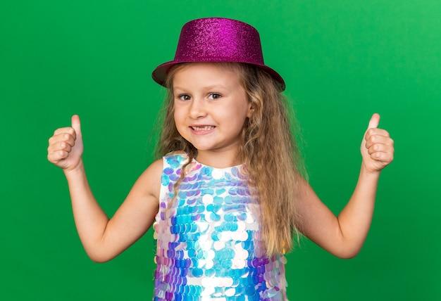 Uśmiechnięta mała blondynka z fioletowym kapeluszem imprezowym kciukami do góry na zielonej ścianie z miejscem na kopię
