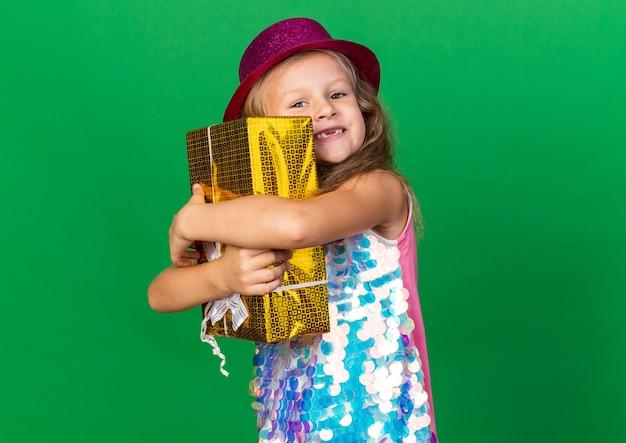 Uśmiechnięta mała blondynka z fioletowym kapeluszem strony przytulanie pudełko na białym tle na zielonej ścianie z miejsca na kopię
