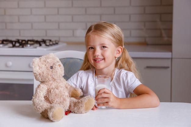 Uśmiechnięta mała blondynki dziewczyna pije mleko w kuchni