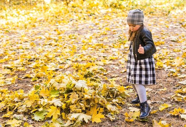 Uśmiechnięta mała dziewczynka bawić się żółtymi liśćmi w jesiennym parku