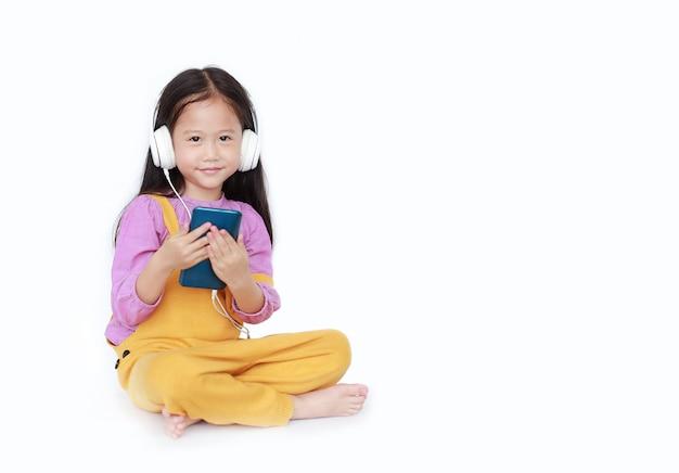 Uśmiechnięta mała dziewczynka cieszy się słuchać muzyka hełmofonami