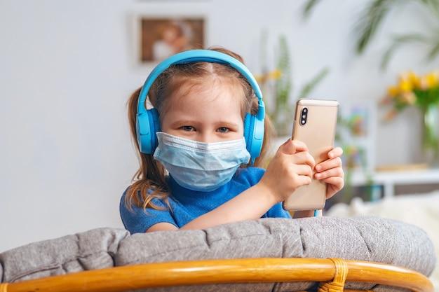 Uśmiechnięta mała dziewczynka dzieciak w masce i błękitnych hełmofonach trzyma telefon komórkowego