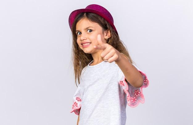 Uśmiechnięta mała dziewczynka kaukaski z fioletowym kapeluszem strony, wskazując na białym tle na białej ścianie z miejsca na kopię