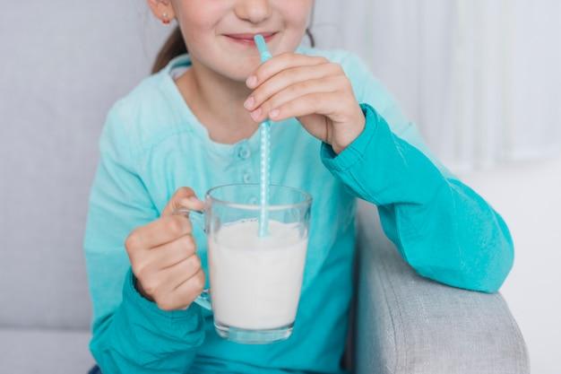 Uśmiechnięta mała dziewczynka pije mleko