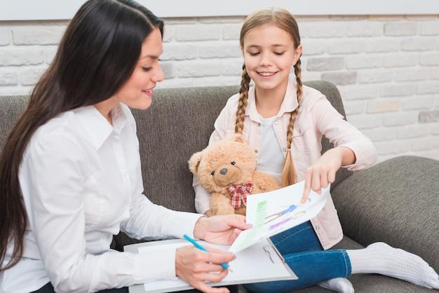 Uśmiechnięta mała dziewczynka pokazuje rysującego rysunkowego papier żeński psycholog