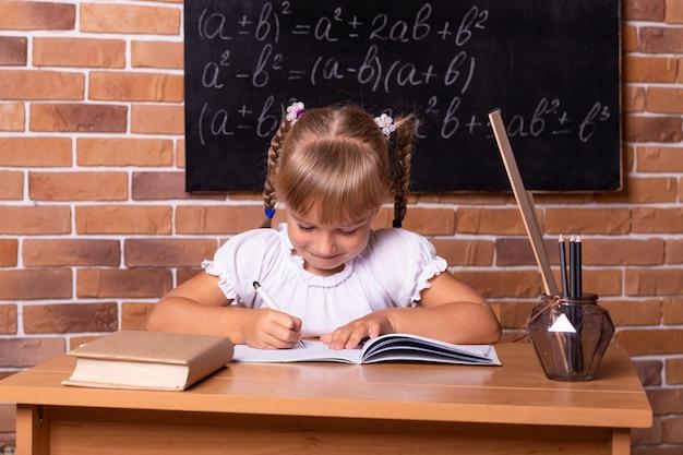 Uśmiechnięta mała dziewczynka student siedzi przy ławce szkolnej i studiuje matematykę.