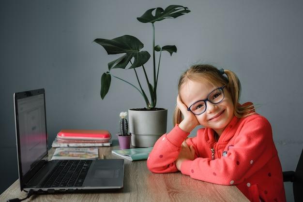 Uśmiechnięta mała dziewczynka studiuje online i używa swojego laptopa w domu, koncepcja nauczania w domu