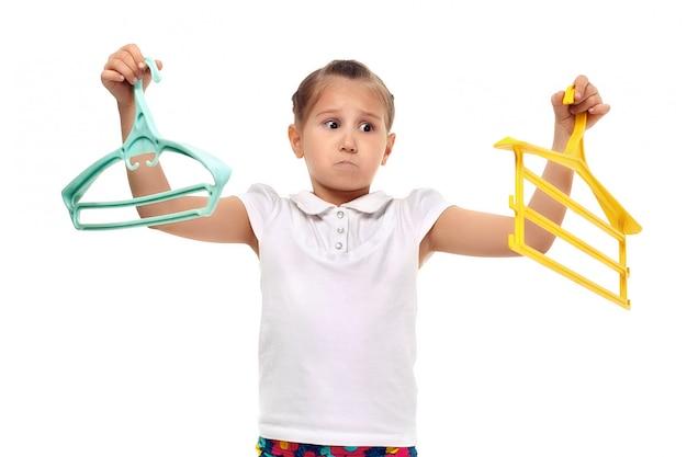Uśmiechnięta mała dziewczynka trzyma koszula w wieszaku. odetnij