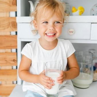 Uśmiechnięta mała dziewczynka trzyma szkło mleko