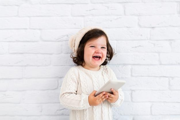 Uśmiechnięta mała dziewczynka trzyma telefon