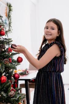 Uśmiechnięta mała dziewczynka w domu w czasie świąt bożego narodzenia dekorowanie choinki w salonie trzymając bombkę bożonarodzeniową
