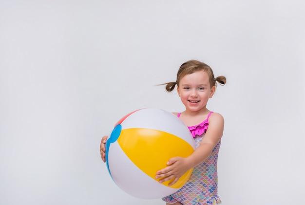 Uśmiechnięta mała dziewczynka w swimsuit z nadmuchiwaną piłką na bielu odizolowywającym