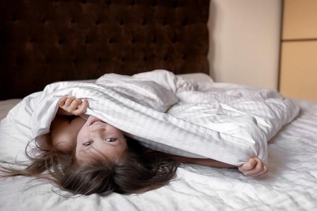 Uśmiechnięta mała dziewczynka wygląda spod kołdry na łóżku w domu patrząc