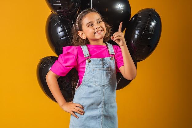 Uśmiechnięta mała dziewczynka z czarnymi balonami w czarny piątek. festiwal niskich cen