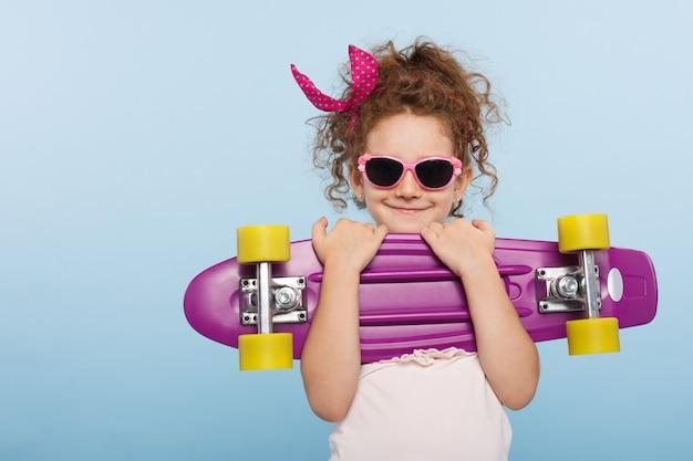 Uśmiechnięta mała dziewczynka z deskorolką