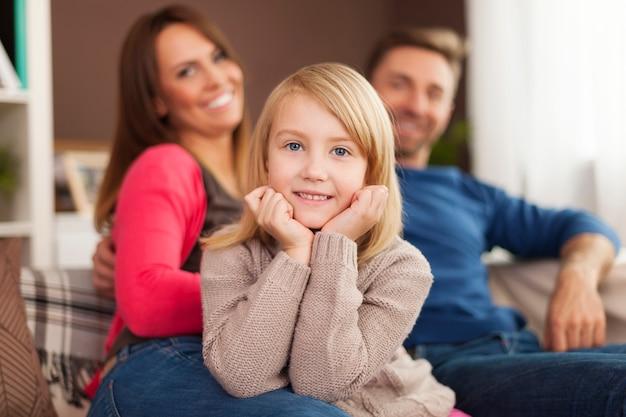 Uśmiechnięta mała dziewczynka z rodzicami w domu