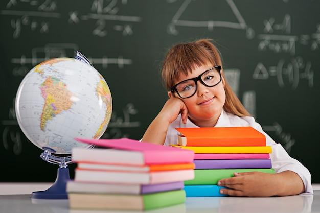 Uśmiechnięta mała dziewczynka ze stosem książek