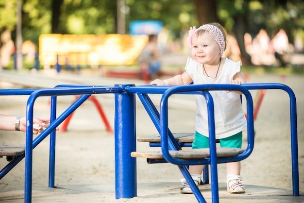 Uśmiechnięta mała dziewczynki pozycja i jeździecki carousel przy boiskiem