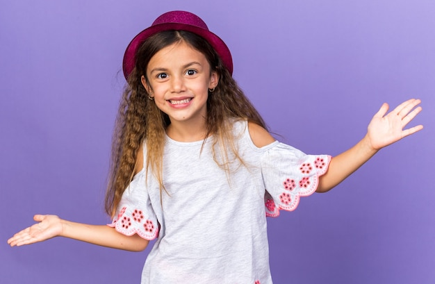 Uśmiechnięta mała kaukaska dziewczyna w fioletowym kapeluszu imprezowym trzymająca otwarte ręce odizolowana na fioletowej ścianie z miejscem na kopię