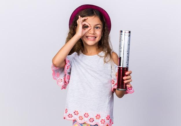 Uśmiechnięta mała kaukaska dziewczynka w fioletowym kapeluszu imprezowym trzymająca armatę konfetti i palcami odizolowana na białej ścianie z miejscem na kopię